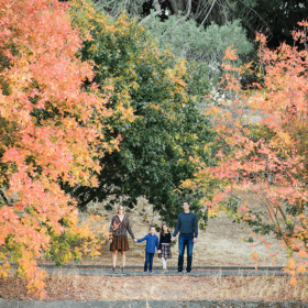 Long overview shot of family standing next to fall foliage trees in Davis