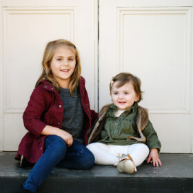 Big sister and baby sister sit on porch step against white doors in Old Sacramento