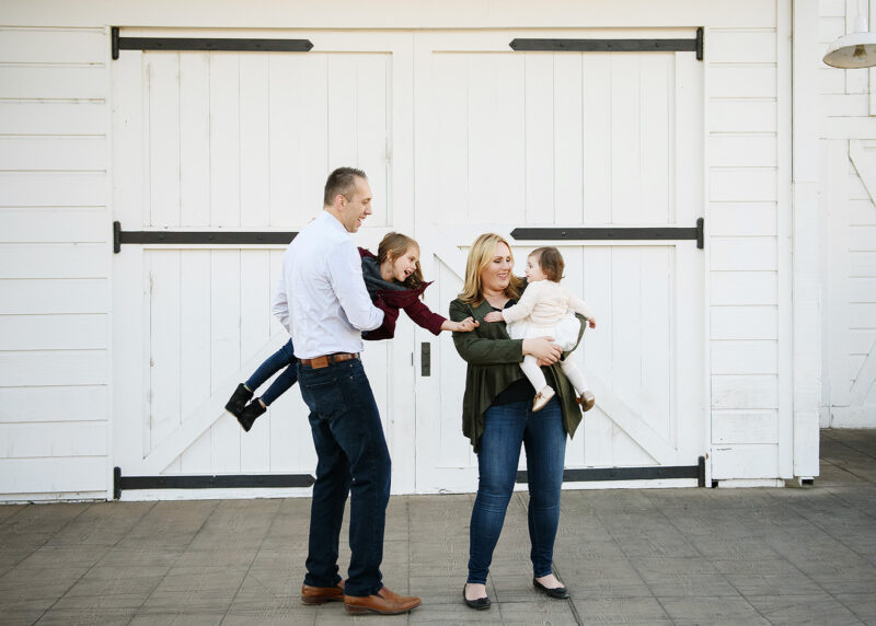 Mom and dad hold daughters as they touch hands and laugh in front of white wooden doors in Old Sacramento