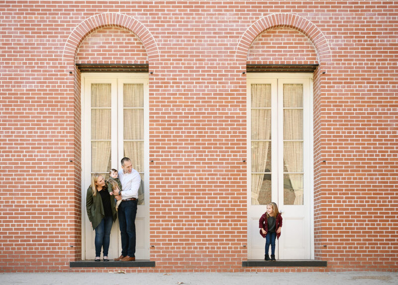 Big sister peeks over to see mom, dad and baby sister on porch step against brick building in Old Sacramento