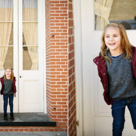 Little girl peeks out from white doors on brick building in Old Sacramento