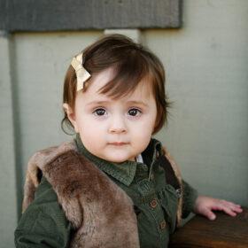 Toddler girl in fur vest looks directly in camera in Old Sacramento