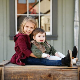 Big sister hugging little sister tight while sitting on crate in Old Sacramento