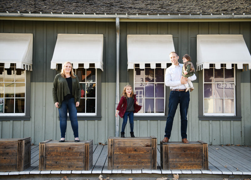 Mom, dad and sister standing on individual crates in Old Sacramento
