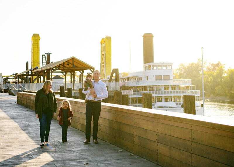 Family walks along Sacramento river with Tower Bridge and ferry in background in Old Sacramento