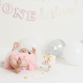 Baby girl falls backwards eating cake during cake smash session in Sacramento studio