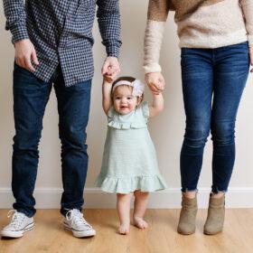 Mom and dad hold baby daughter's hands on wooden floor in Sacramento studio