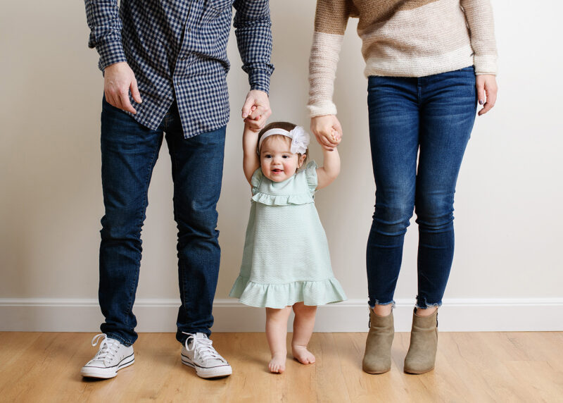 Mom and dad hold baby daughter's hands on wooden floor in Sacramento studio
