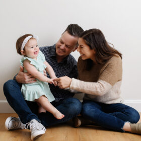 Mom and dad make baby daughter laugh while sitting on the floor in Sacramento studio
