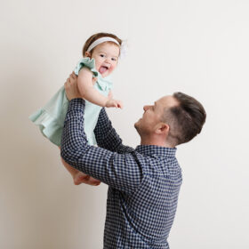 Dad holds up baby daughter as she sticks out her tongue in Sacramento studio.