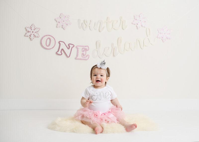 Baby girl in pink tutu sitting on sheepskin and winter wonderland sign in Sacramento studio
