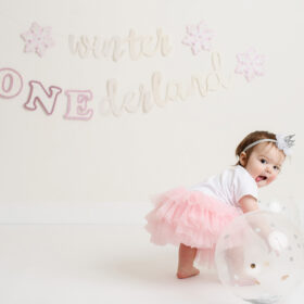 Baby girl in tutu sticking out her tongue and grabbing a balloon in Sacramento studio