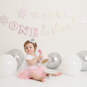 Baby girl in pink tutu grabbing cake in Sacramento studio cake smash