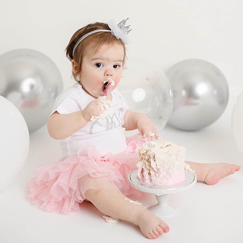 Baby girl in pink tutu eating and smashing her birthday cake in Sacramento studio