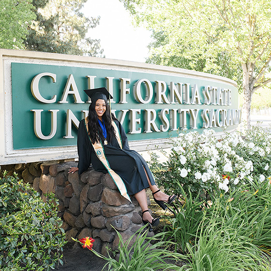 Sacramento State Senior Girl in front of university sign in cap and gown