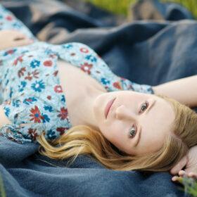 Teen girl lying down on blue blanket in Sacramento