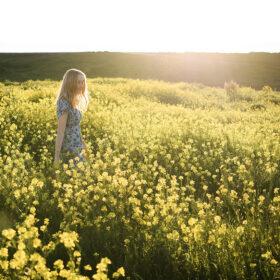 Teenage girl walking through yellow wildflowers with sun in her hair in Sacramento