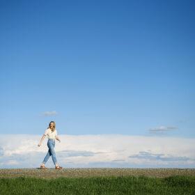 Teen girl walking against big blue sky horizon in Sacramento