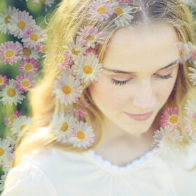 Double exposure image of teen girl with wildflowers in hair