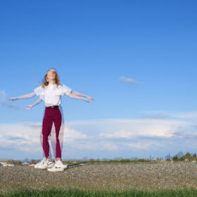 Double exposure movement of teen girl in large blue sky horizon