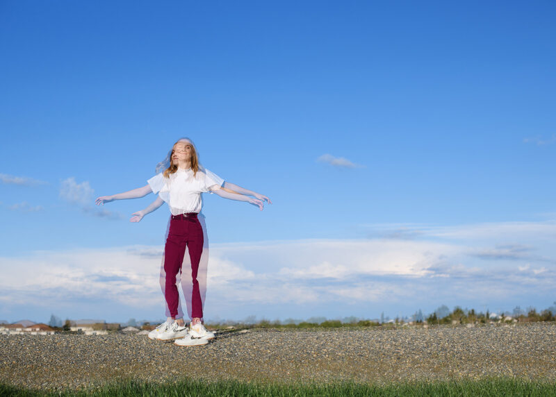 Double exposure movement of teen girl in large blue sky horizon
