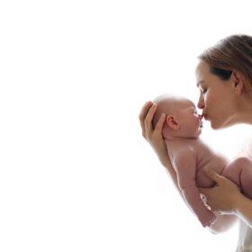 Mom kissing newborn baby boy against white light background in home