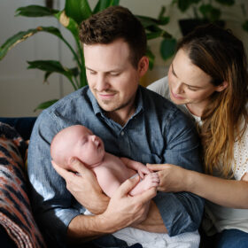Mom and dad hold newborn baby boy while sitting on couch at home lifestyle session