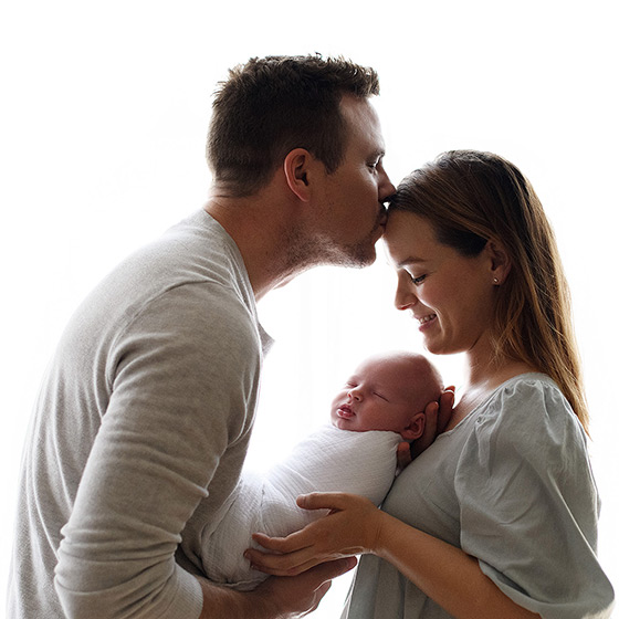 Dad kissing mom's head while holding sleeping newborn baby
