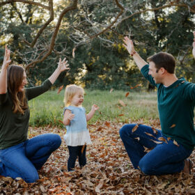 Mom and dad toss brown leaves in the air as toddler daughter smiles in Sacramento