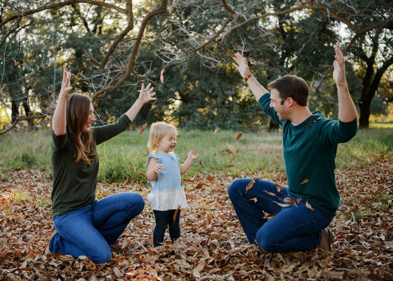 Mom and dad toss brown leaves in the air as toddler daughter smiles in Davis