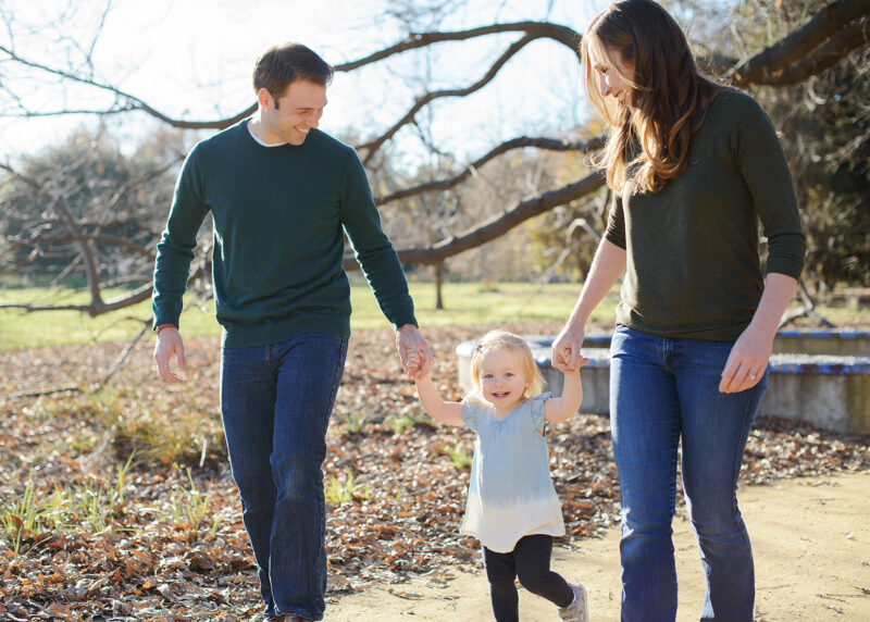 Mom and dad hold toddler daughter's hands as they walk through Sacramento park