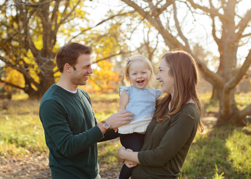 Mom and dad smile while holding toddler daughter laughs with foliage in background
