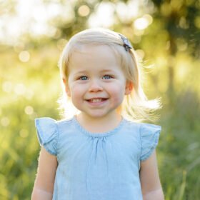 Toddler girl smiling directly at camera with trees and grass in background Sacramento
