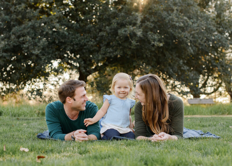 Mom and dad lie on grass while looking at toddler daughter with green trees in background Sacramento