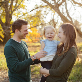 Mom holding toddler daughter smiling as dad smiles happily in park outdoors