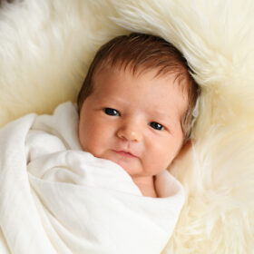 Newborn baby with eyes open staring directly in camera on sherpa throw in Sacramento studio