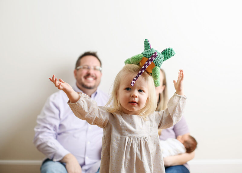 Toddler girl throwing colorful toy in air as mom and dad watch in background in Sacramento studio