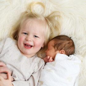 Big sister smiling and lying next to sleeping newborn sibling on sherpa throw in Sacramento studio