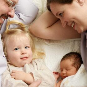 Mom, dad and big toddler sister lying next to sleeping newborn baby in Sacramento studio