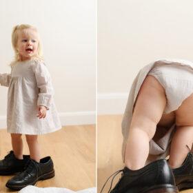 Toddler girl wearing dad's black shoes in Sacramento studio