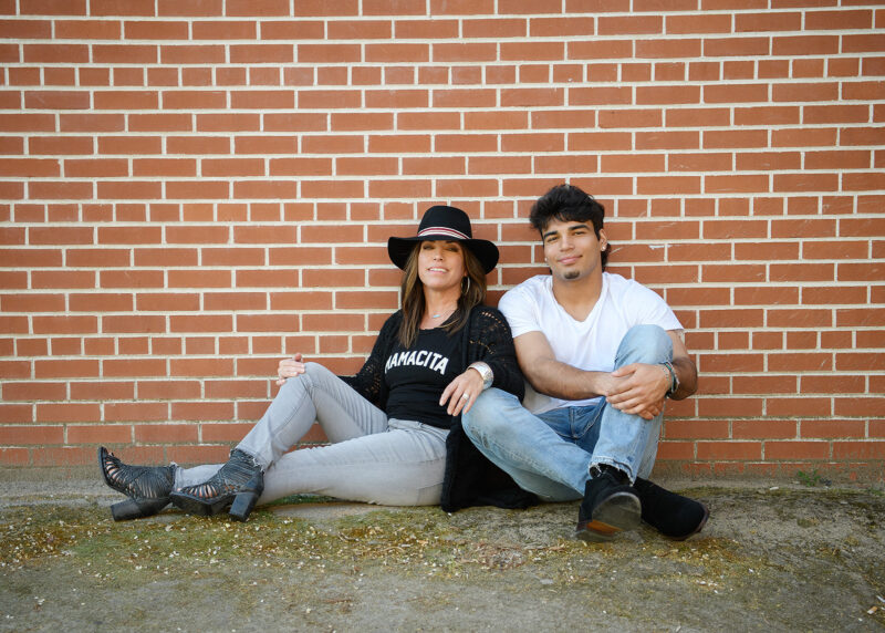Teenage boy with his mom sitting on ground against brick background in Old Sacramento