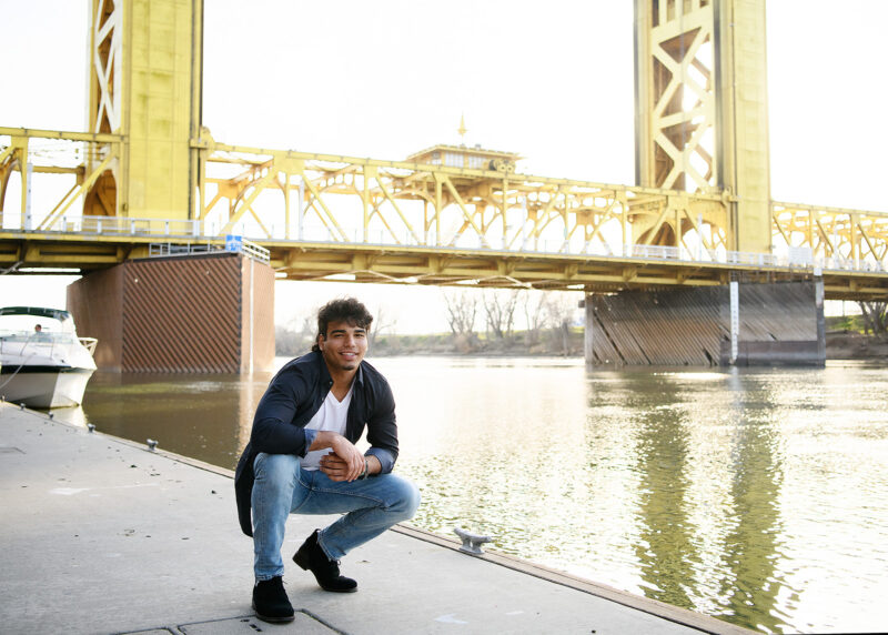 High school senior boy squatting at Sacramento waterfront and Tower Bridge in background