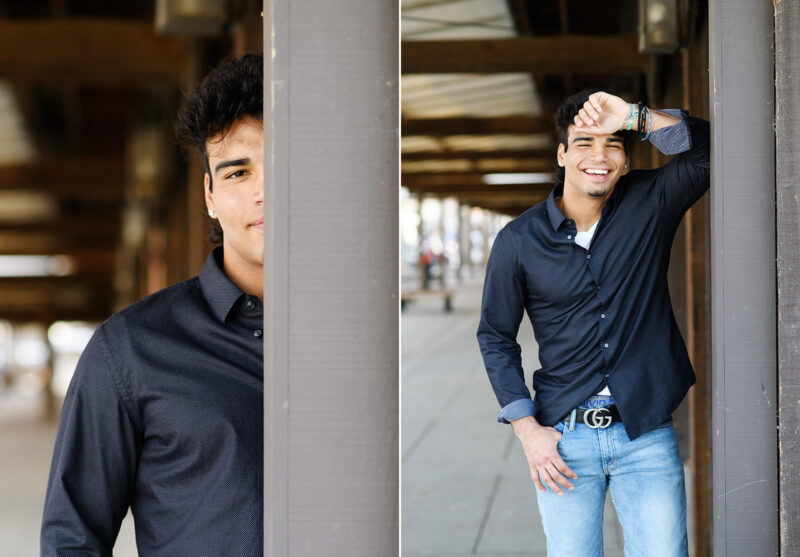 High school senior boy leaning against Sacramento waterfront pier and smiling
