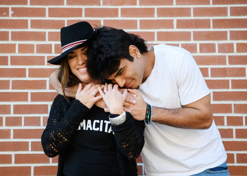 High school senior boy hugging his mom against red brick background in Old Sacramento