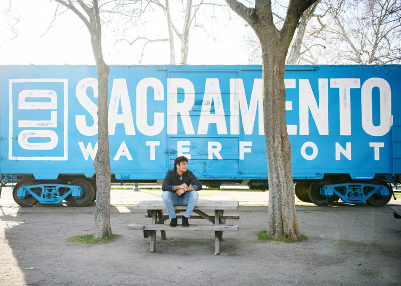 High school senior boy sitting on bench in front of blue train in Old Sacramento