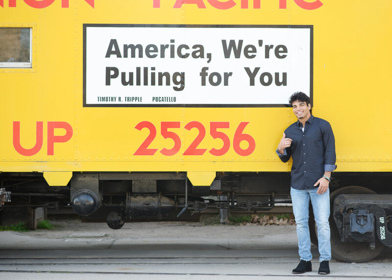 Teenage boy pointing at yellow train that says America, we're pulling for you in Old Sacramento