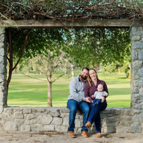 Dad and mom sit down under stone pagoda while holding baby boy in Davis