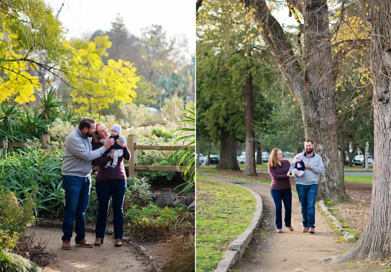 Mom and dad walk along dirt path while holding son and smiling in Davis
