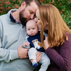 Mom and dad kiss baby son outdoors in Davis