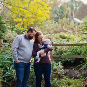 Mom holds baby boy while dad looks lovingly surrounded and framed by green trees and bushes in Davis